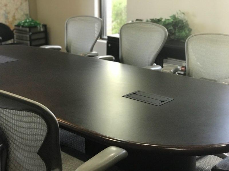 oblong dark wood conference table with six gray office chairs