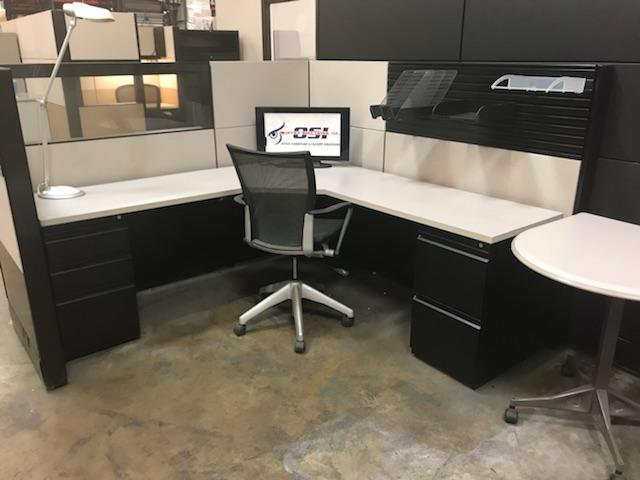black and white workstation with white desktop and black base with two cabinets, two drawers each. Has white and black panel backing