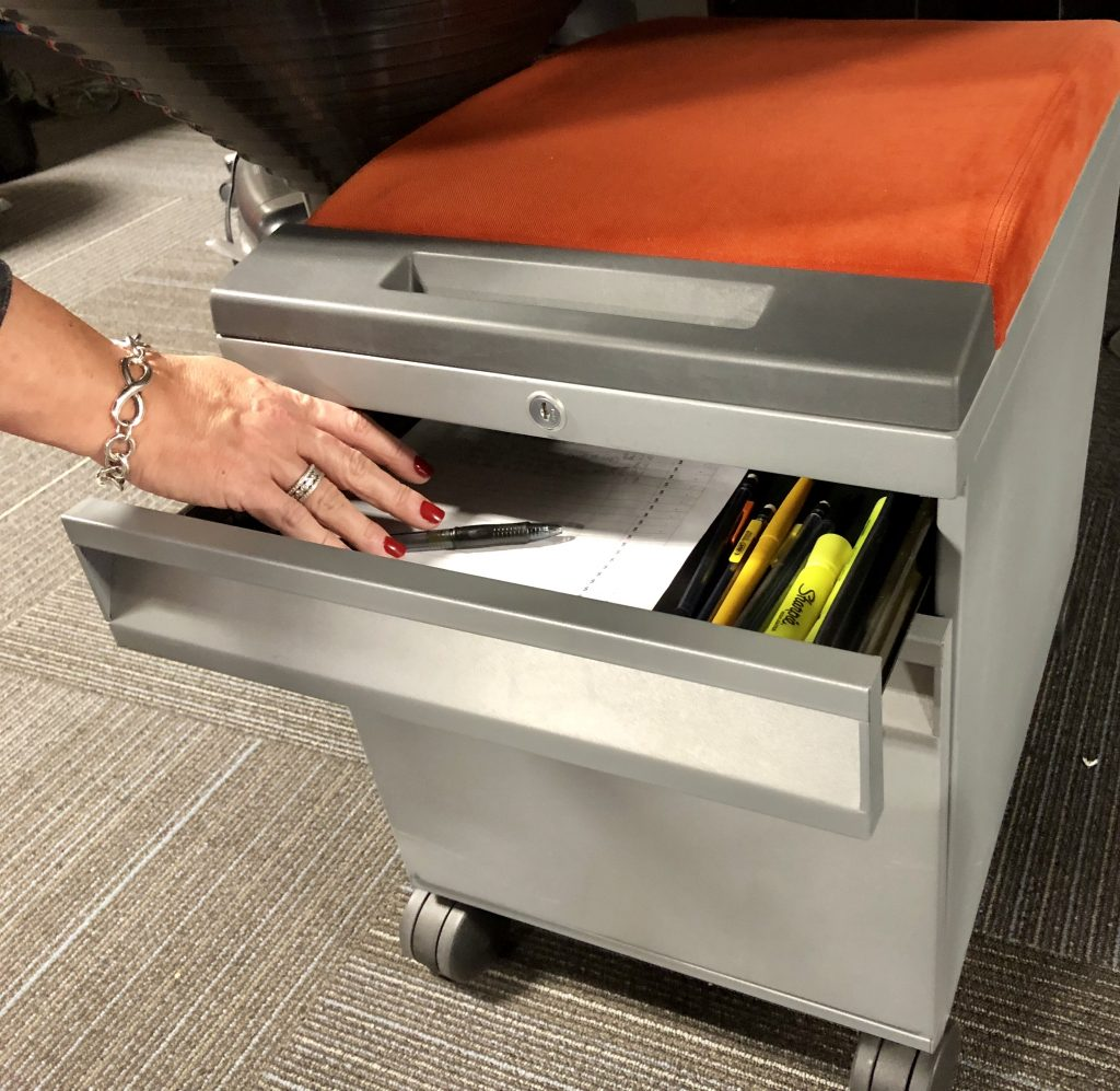 metal mobile station with orange padded and top drawer open