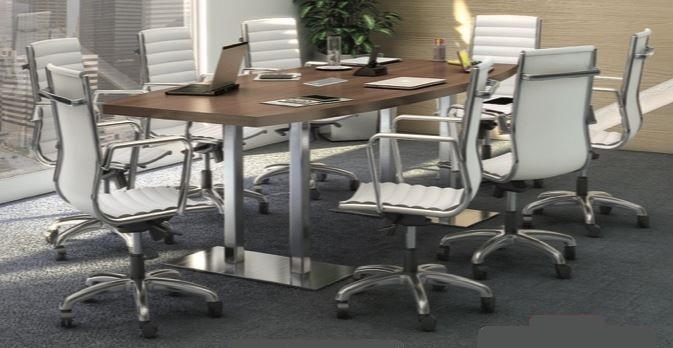 wood top silver base conference table with eight white and silver office chairs with wheels.