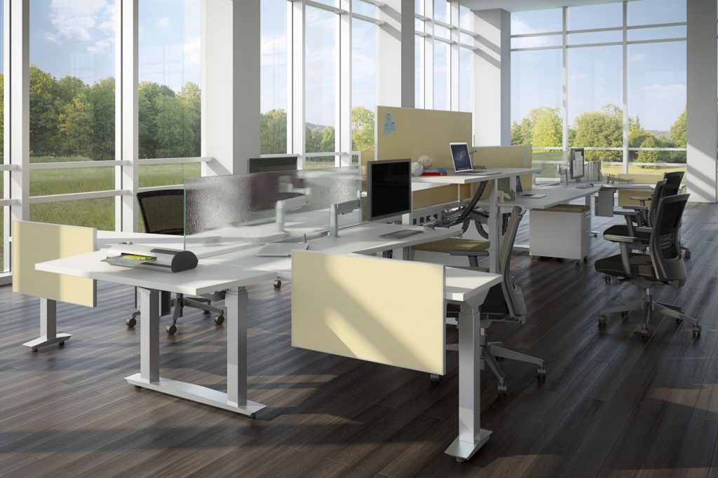 loft with four white desks with adjustable heights. Desks have creme and white half size dividers and flatscreen desktops