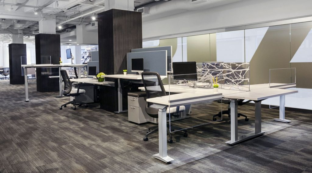 loft with four white desks with glass side panes, four black metal chairs and one large black wood lateral