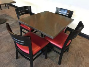 breakroom table with granite top and four chair with black frames and back and red cushions