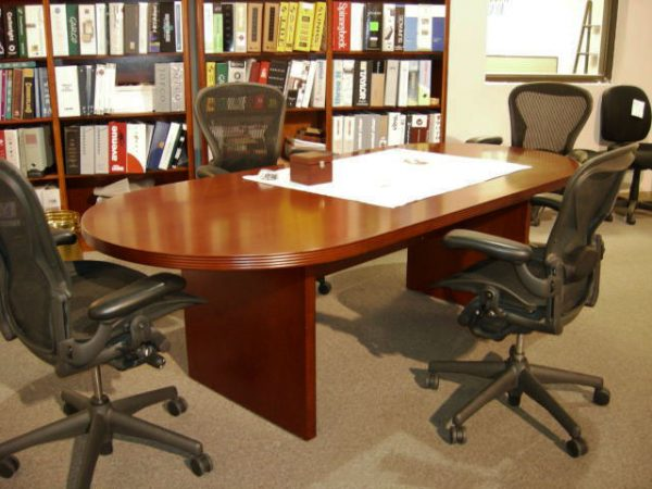 cherry conference table and four gray chairs with white paper on top and cherry wood box