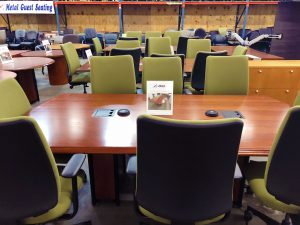 cherry conference table with 8 green chairs and two gray metal plugs