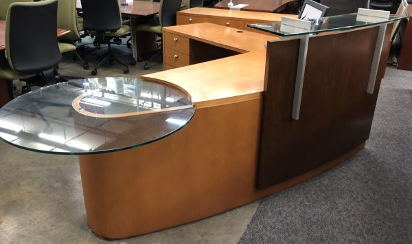 contemporary wood reception desk with darker wood front fixture with glass top. Circular glass table at end of desk