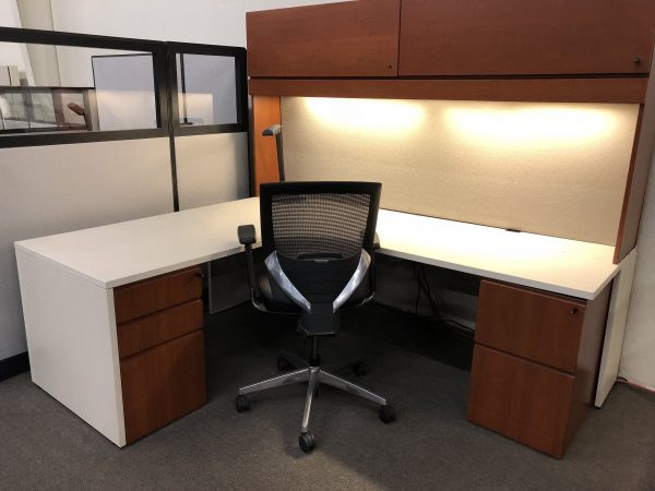 desk with white top, cherry drawers and overhead cabinets and black and metal chair