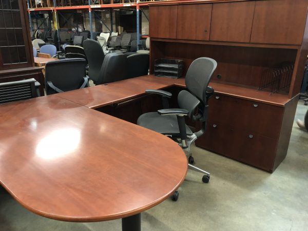 cherry desk with black hair, two black folder holders, overhead cabinets and four drawers