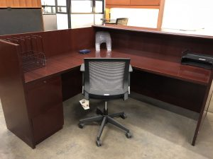 mahogany reception desk with two black folder holders and silver square chair and a set of drawers