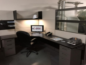 dark gray workstation with white wall, window and black chair.