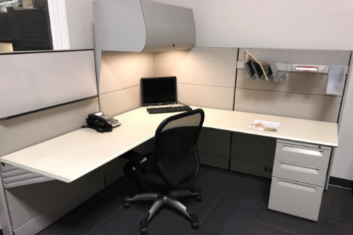white workstation with overhead drawer, black phone and black chair