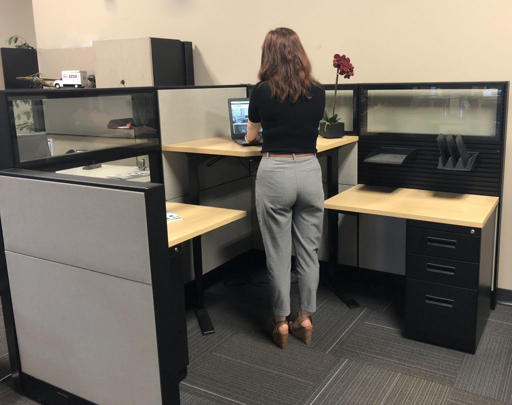 Woman working at sit-to-stand cubicle