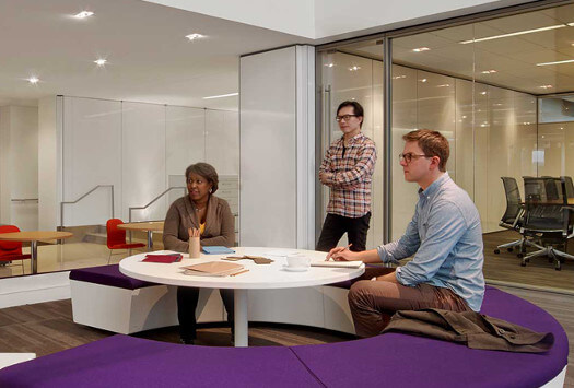 three people in a conference room. Two sitting on a circular purple padded bench around a white table. One man in classes writing in a pad, one woman is listening and another is standing up with arms crossed.
